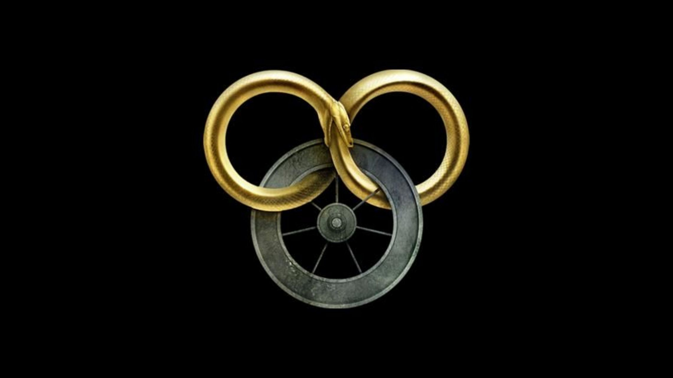 Against a black backdrop, there's a seven-spoked wheel that looks like it's made of iron. Intertwined is a gold-colored snake eating its own tail, twisted into an infinity symbol.